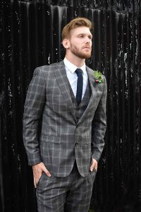 Groom in a grey checked suit with black tie