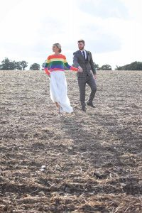 bride wearing rainbow jumper and groom in a field