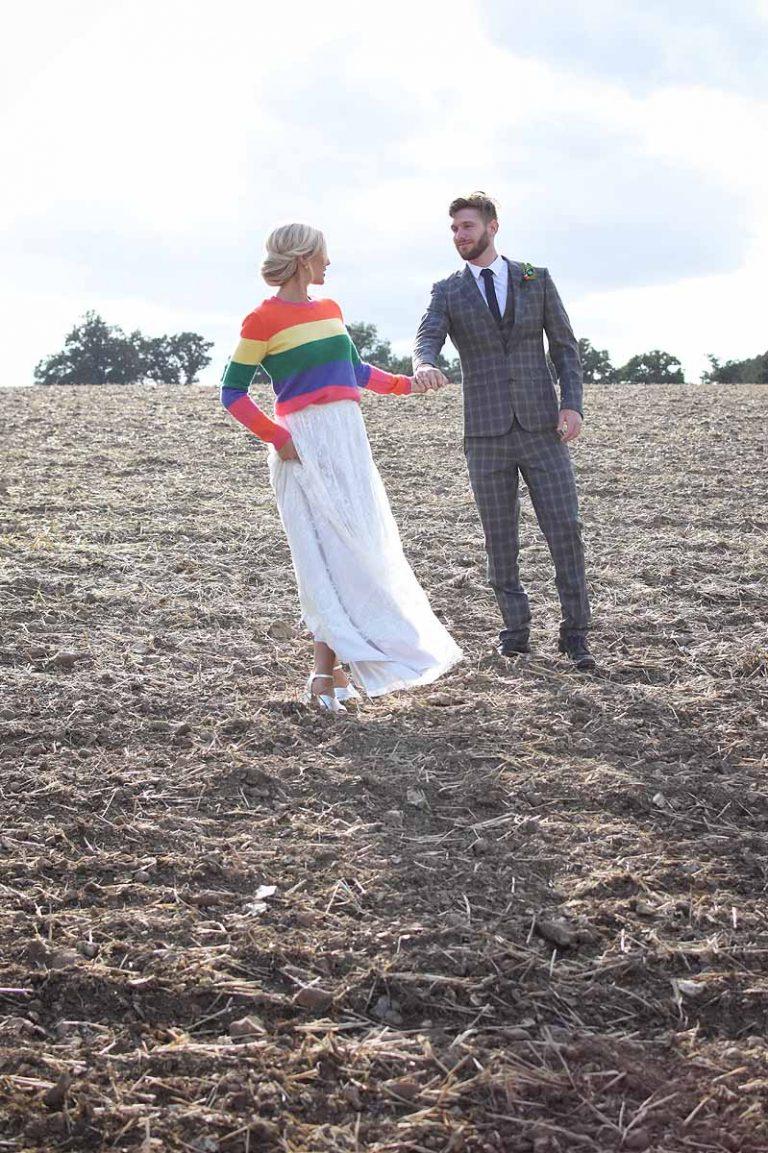 bride in rainbow jumper looking back at groom