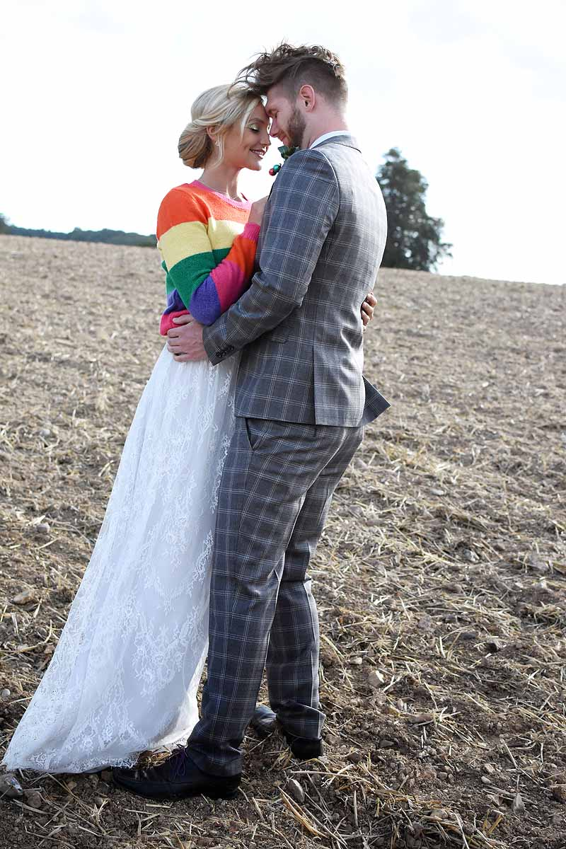 bride in rainbow jumper and groom in grey suit in a dry soil field