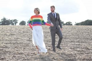 bride in rainbow jumper with groom in a field