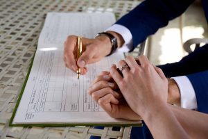 The signing of the wedding register with a gold pen and showing engagement and wedding rings