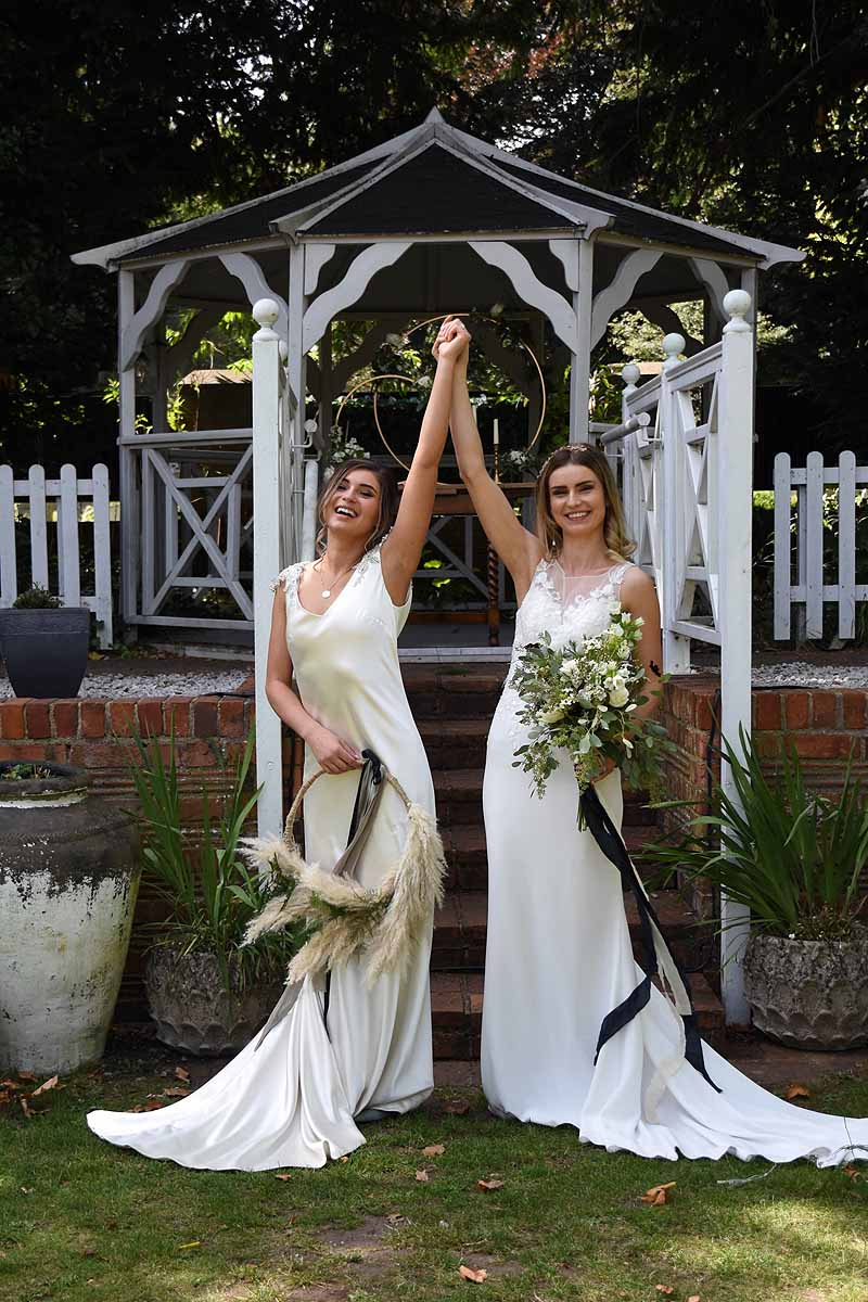 two brides cheering with clasped hands in the air