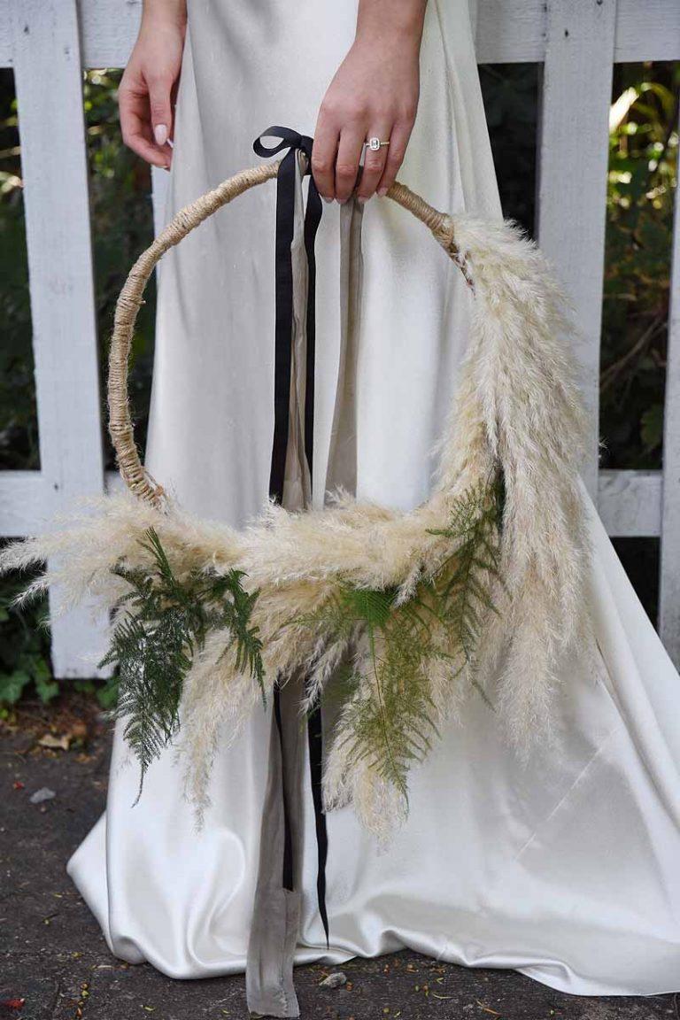 hoop flower arrangement with pampas grass and asparagus fern