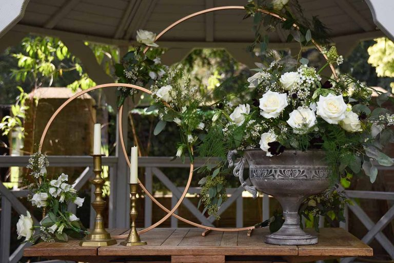 Brass hoop and antique urn filled with white avalanche roses and greenery