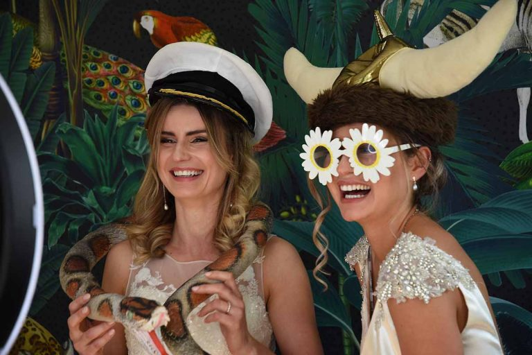 Two brides in fancy dress in a photobooth