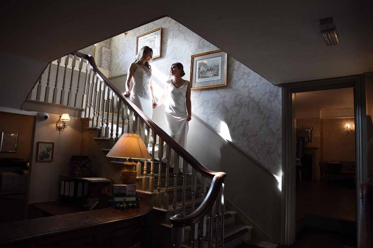 Two brides on the stairs at the Elephant Hotel Pangbourne