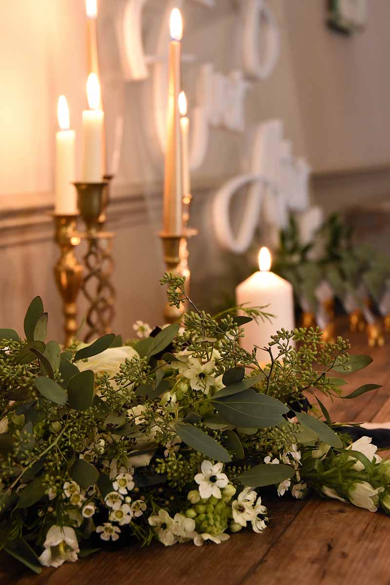 white candles and white and green floral arrangement