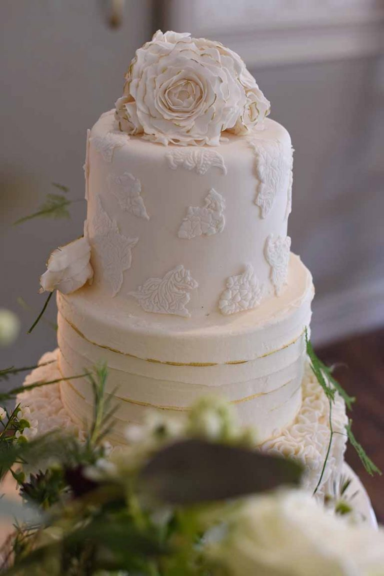 three tier wedding cake with gold and rose decoractions