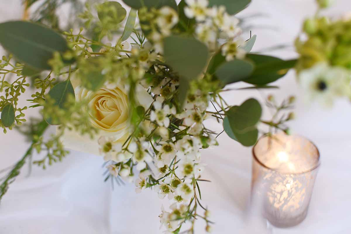 white rose and green foliage table decoration with gold tealight candle holder