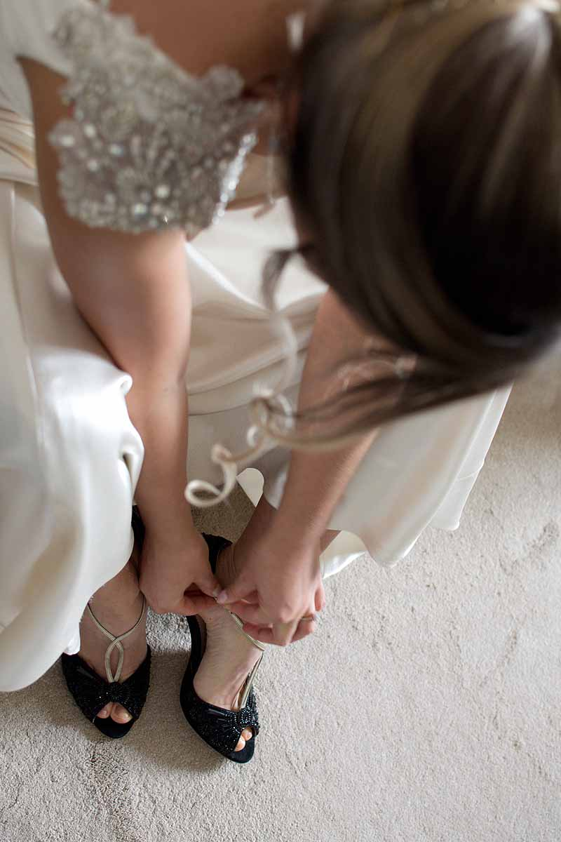 bride putting on black and gold Emmy London shoes