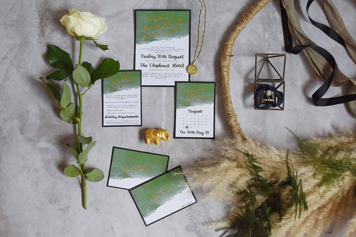 Green, white, black and gold wedding stationery and other wedding accessories