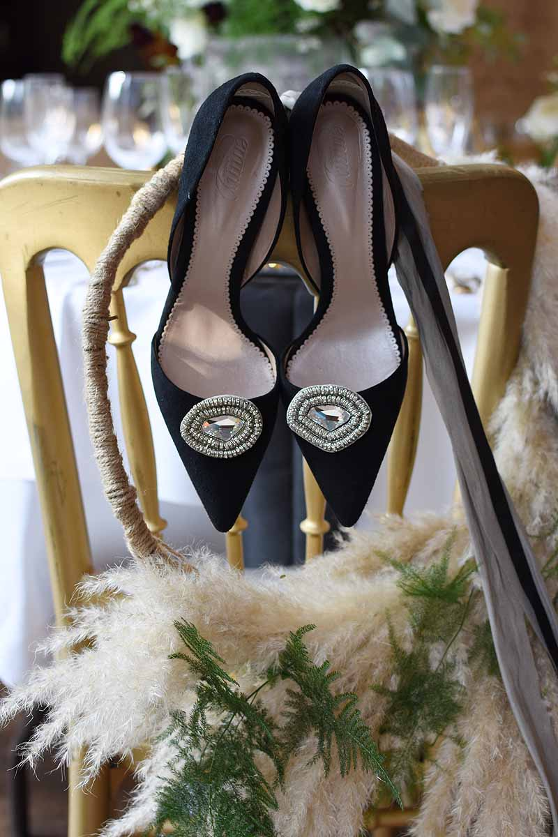 Black Emmy London shoes with hoop pampas grass and asparagas fern arrangement