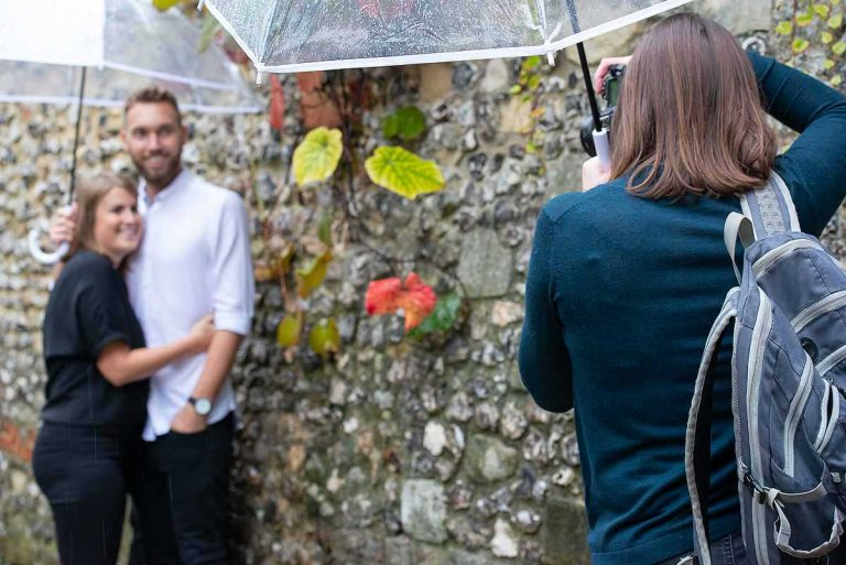 couple being photographed next to a wall with autumn foliage