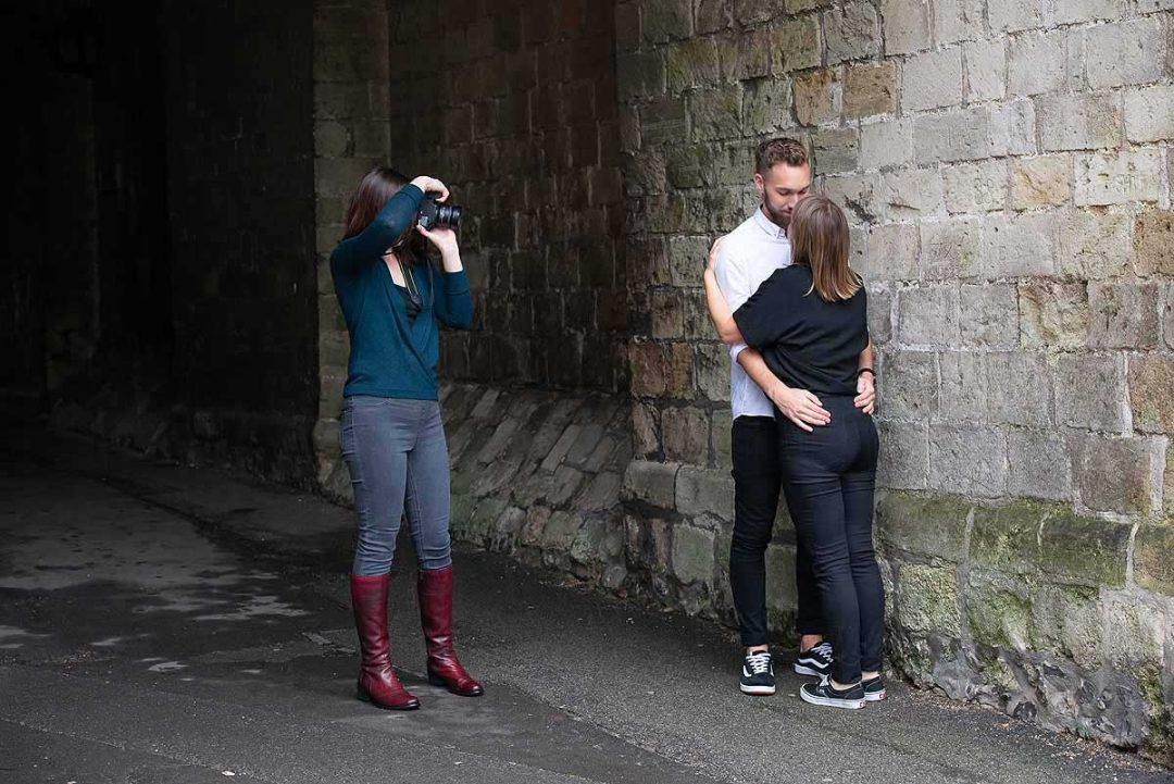 couple being photographed next to a wall