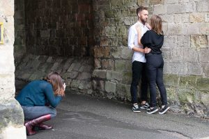photographer on the ground taking photo of couple