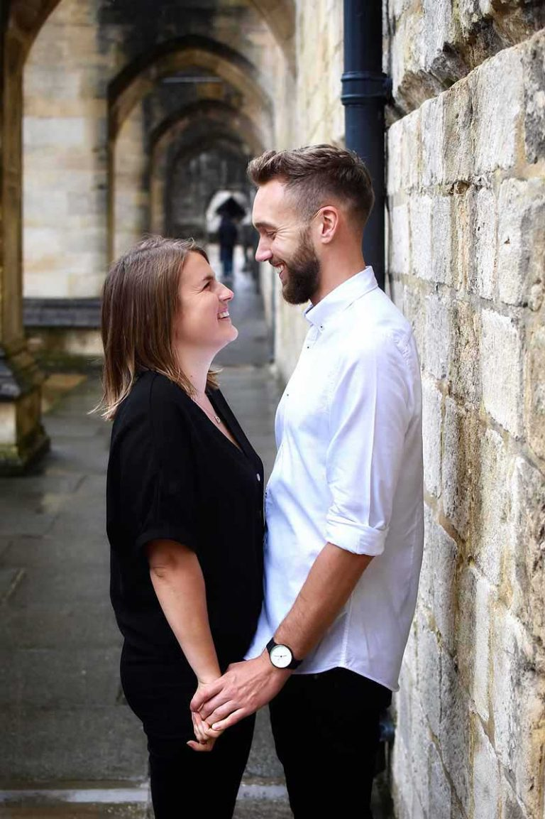 couple standing in the cloisters of Winchester Cathedral holding hands