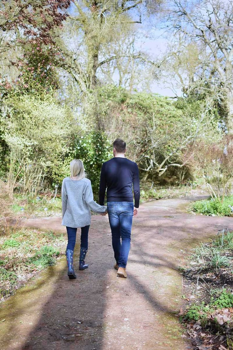 couple walking in a garden filled with sunshine