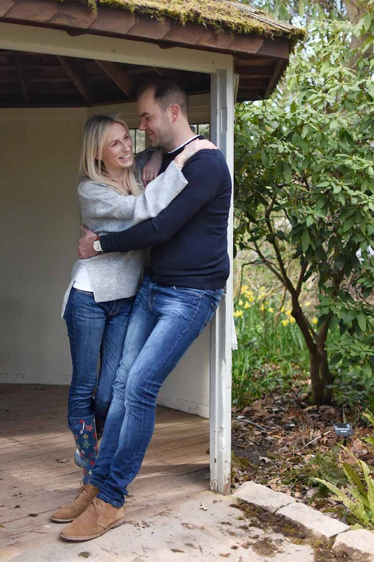 couple standing in the doorway of a garden pergola