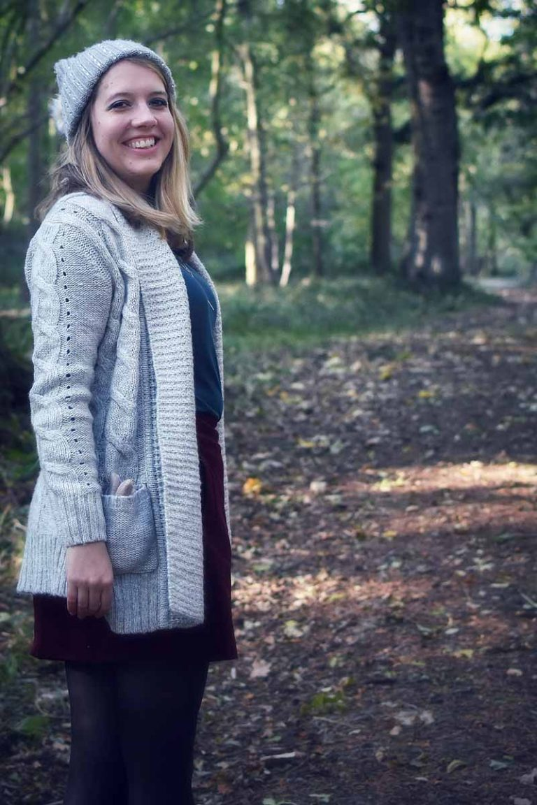 Emily in long grey cardigan and grey wooly hat in Wytham Woods