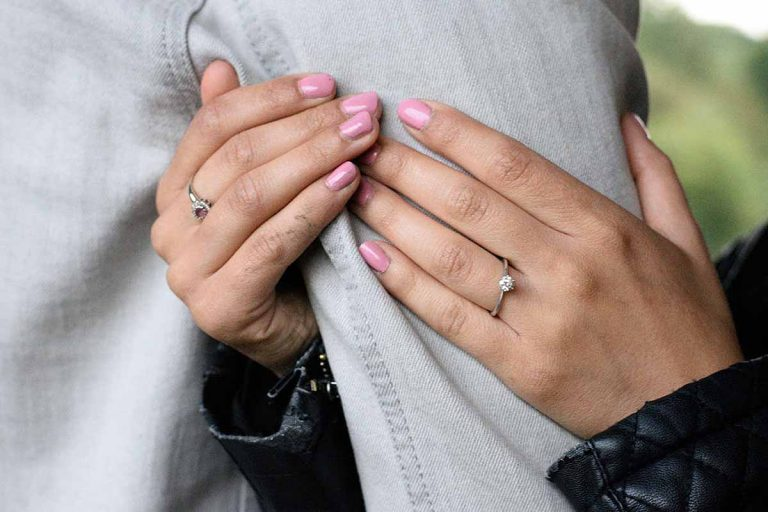 ladies hands with rings and pink nail polish