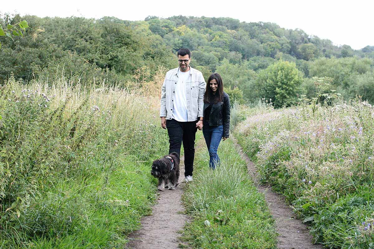 couple walking in wild flower meadow with their dog