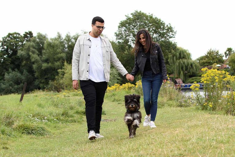 dog bounding forwards with couple holding hands