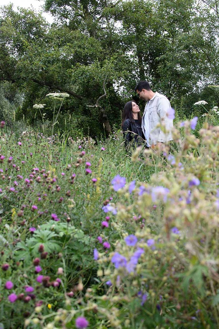 couple standing in a while flower meadow in Berkshire