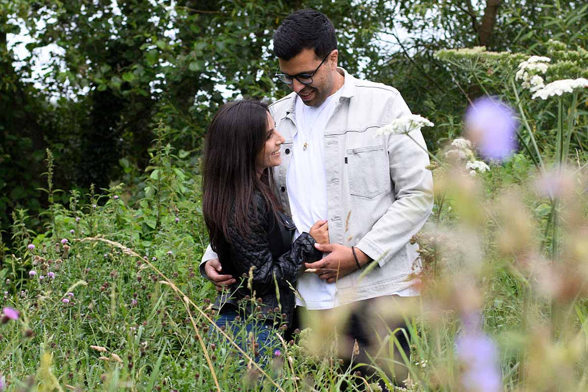 couple standing in a wild flower meadow