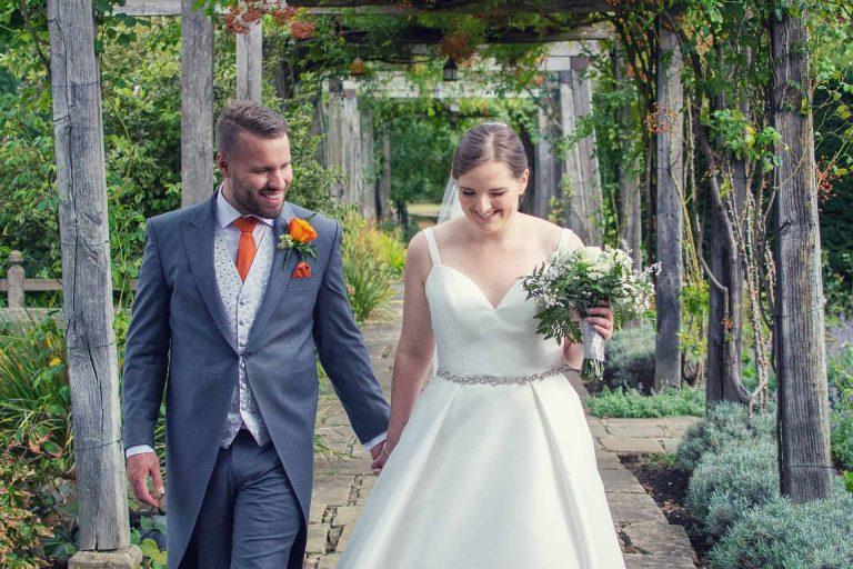 Bride and groom walking in a garden