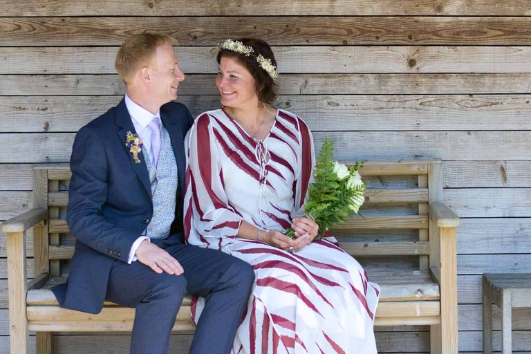 Bride and groom sitting on a wooden bench looking adoringly at each other