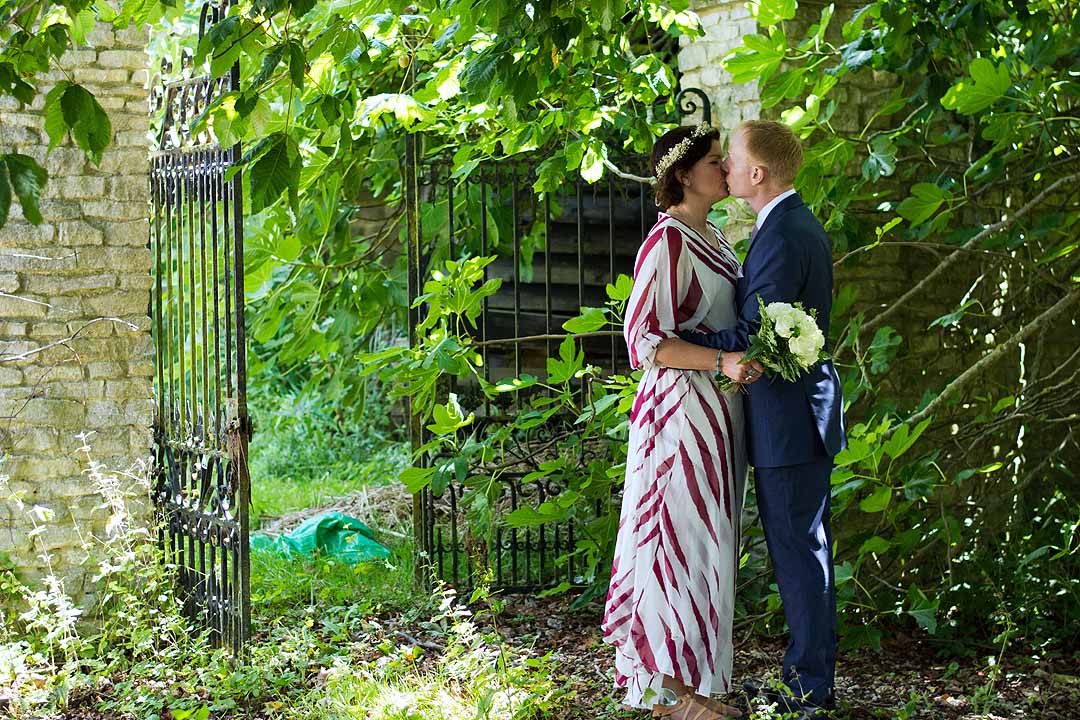 bride and groom kissing in a wild garden