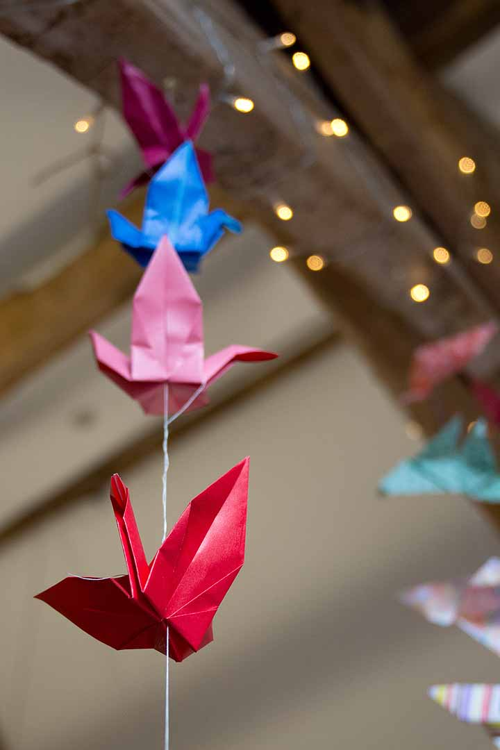 Colourful origami birds strung from wooden beams