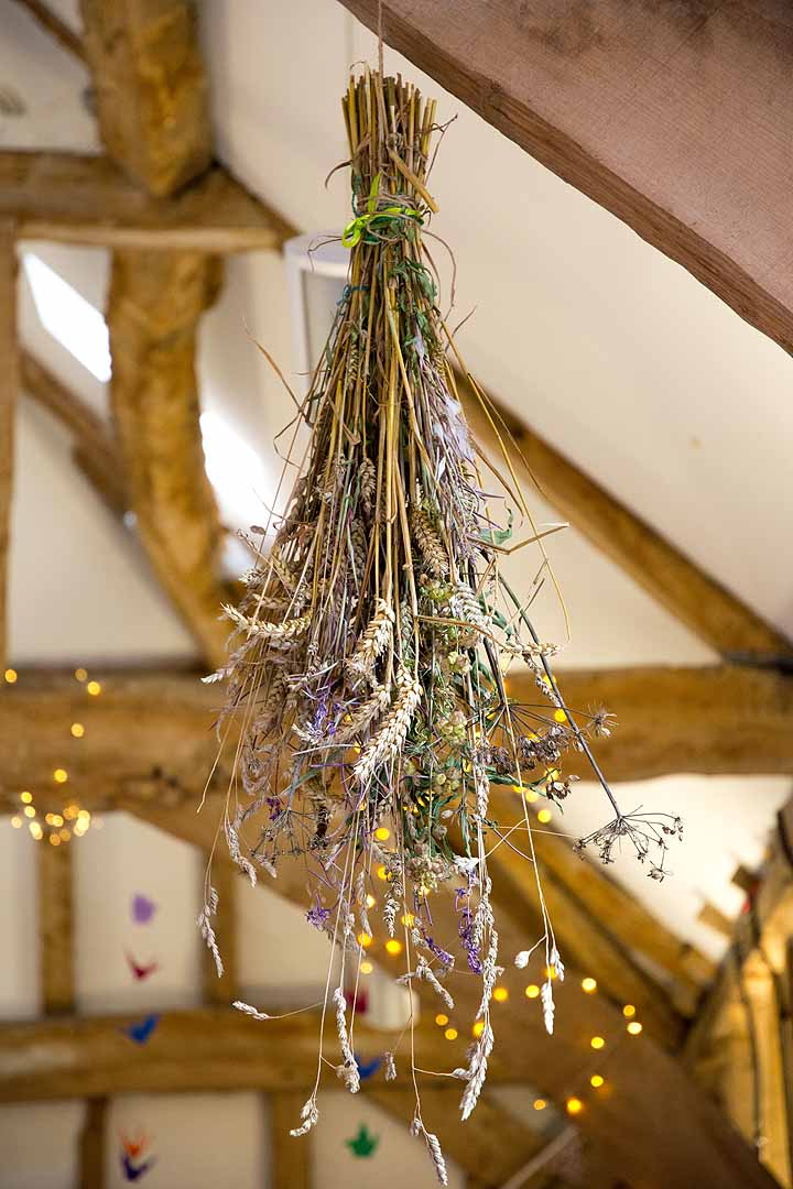 dried flowers hanging from a barn roof