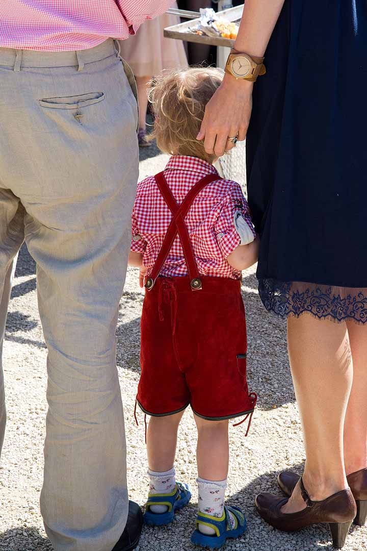 Boy in red lederhosen with parents