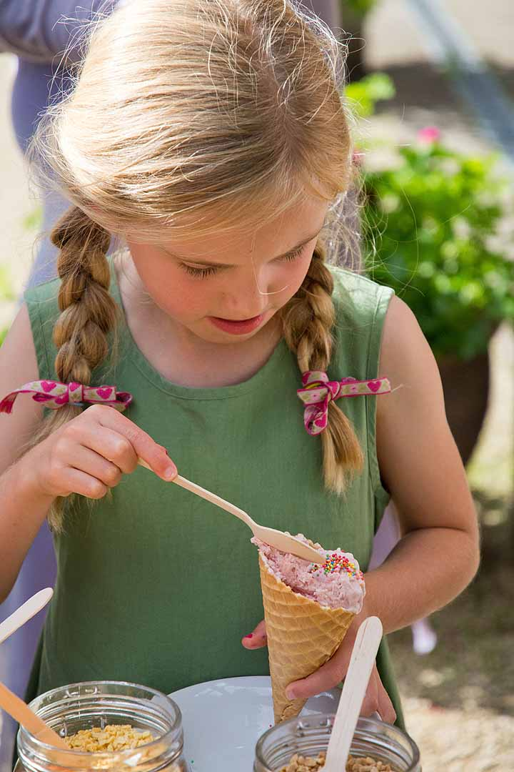 Girl with blonde pigtails adding sprinkles to her ice cream