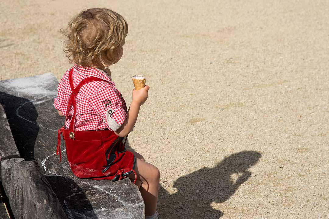 Boy in red lederhosen eating an ice cream