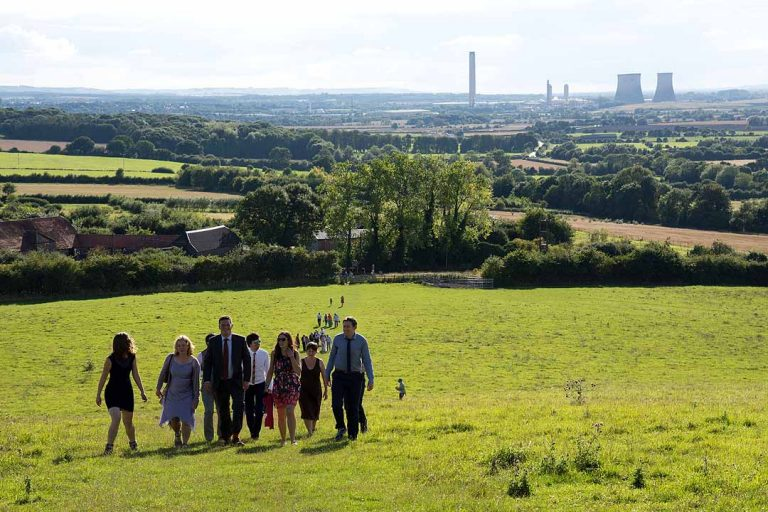 Wedding guests walking up Wittenham Clumps with Didcot power station in the background