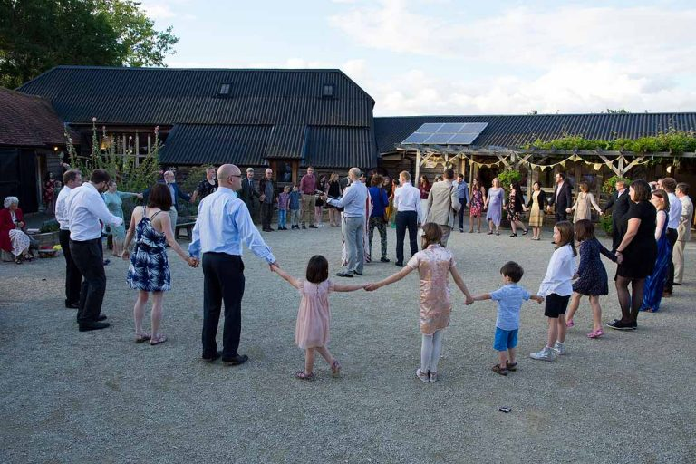 people holding hands in a circle outside the fison barn, Oxfordshire