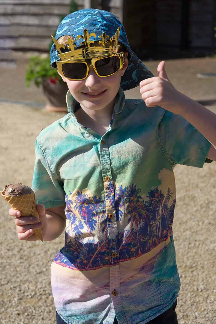 Boy with gold crown sunglasses, baseball cap and an ice cream