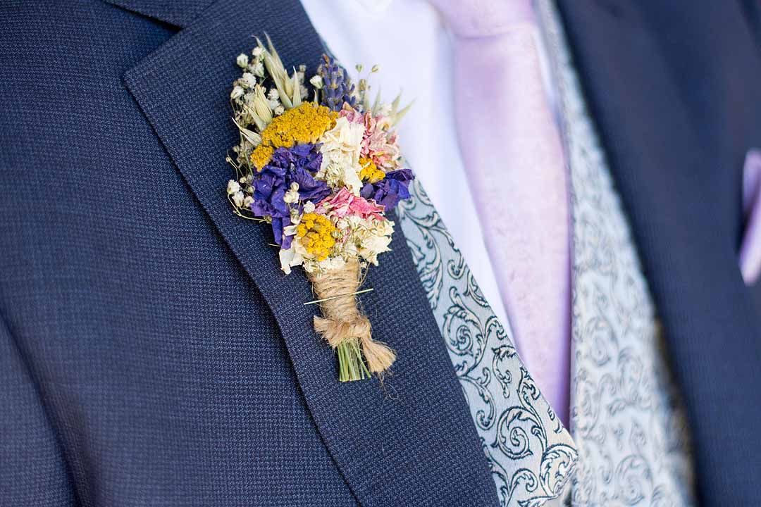dried flower button hole pinned to blue suit
