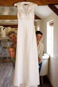 three bridesmaids peeking behind a wedding dress