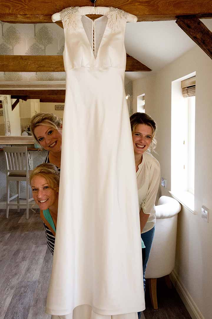 three bridesmaids peeking behind a wedding dress