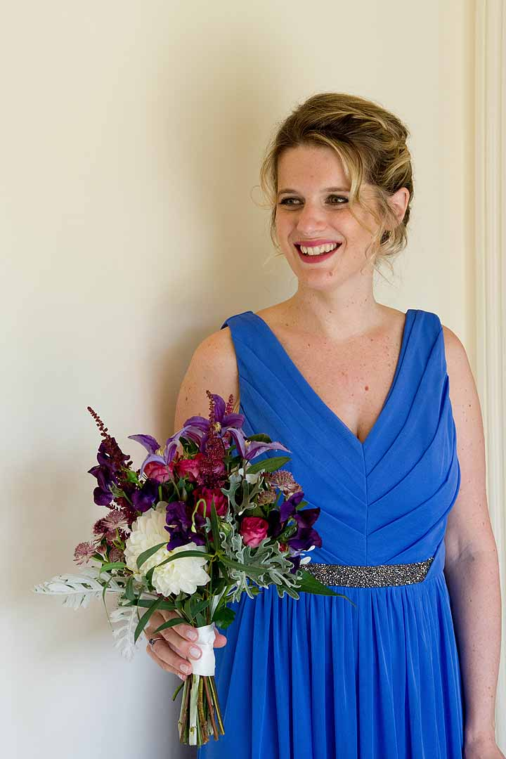 Bridesmaid in cornflower blue dress holding bouquet