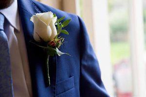 white rose button hole on a blue suit
