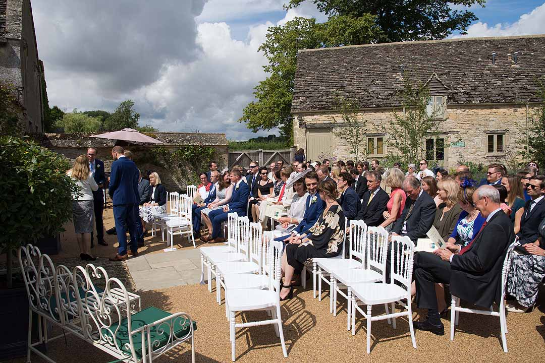 wedding guests seated for outdoor ceremony at Caswell House Oxfordshire