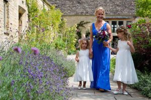 Bridesmaid in blue dress with two flower girls in white in a lavender garden