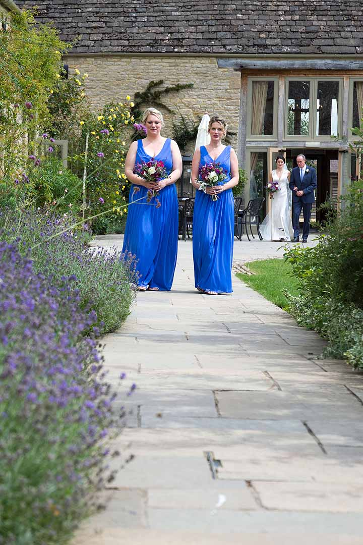 two bridesmaids in blue dresses walking down a lavender lined path