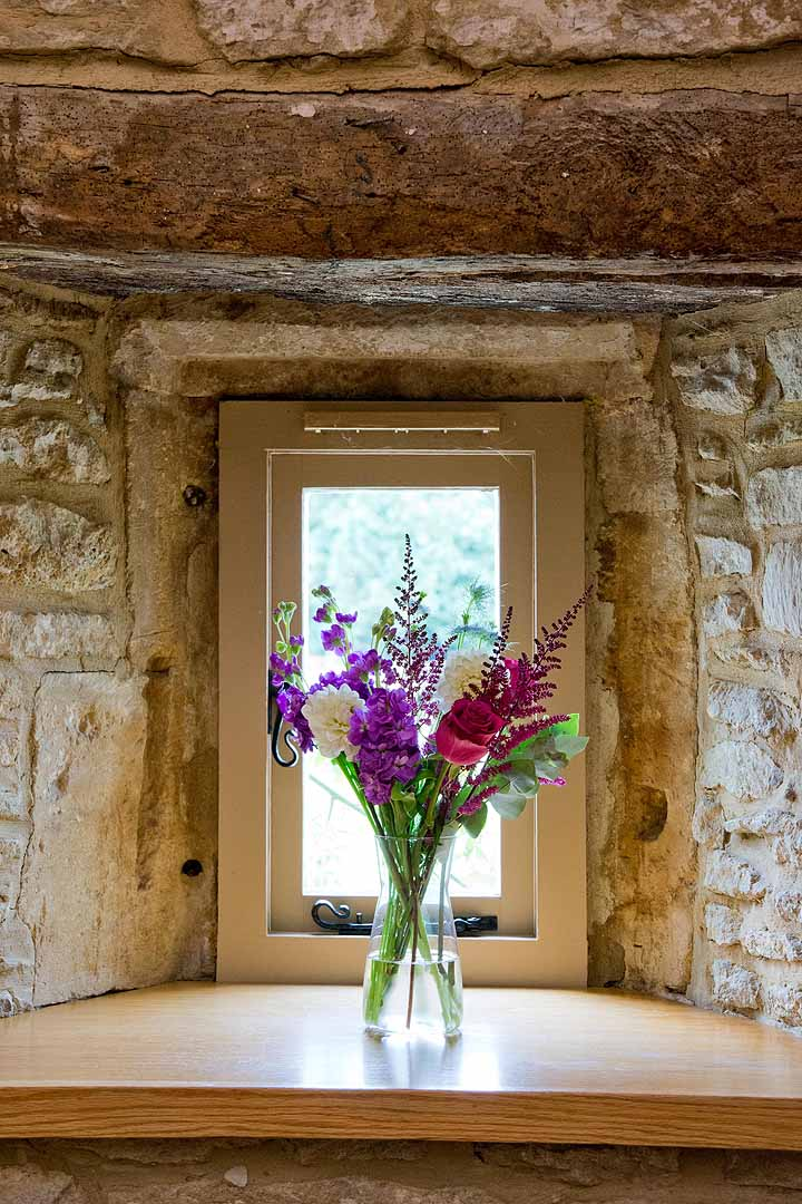 pink and purple wedding flowers in a barn window