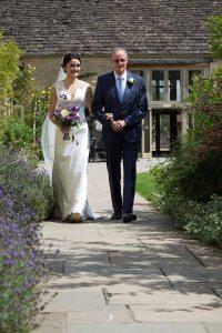 bride and her father walking in a garden